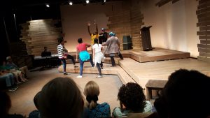 Cast members performing a scene from the play